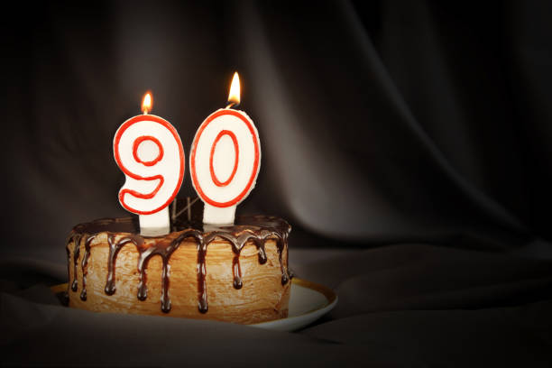 ninety years anniversary. birthday chocolate cake with white burning candles in the form of number ninety. dark background with black cloth - number 90 stock photos and pictures