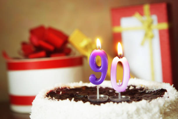 ninety years birthday. cake with burning candles and gifts - number 90 stock photos and pictures