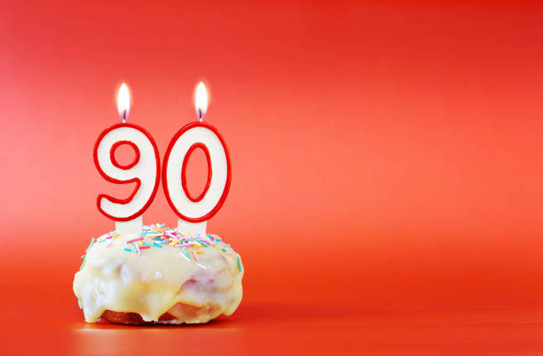 ninety years birthday. cupcake with white burning candle in the form of number 90. vivid red background with copy space - number 90 stock photos and pictures