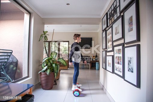 A Nine-year-old boy riding his motorized hoverboard in the hallway at home.