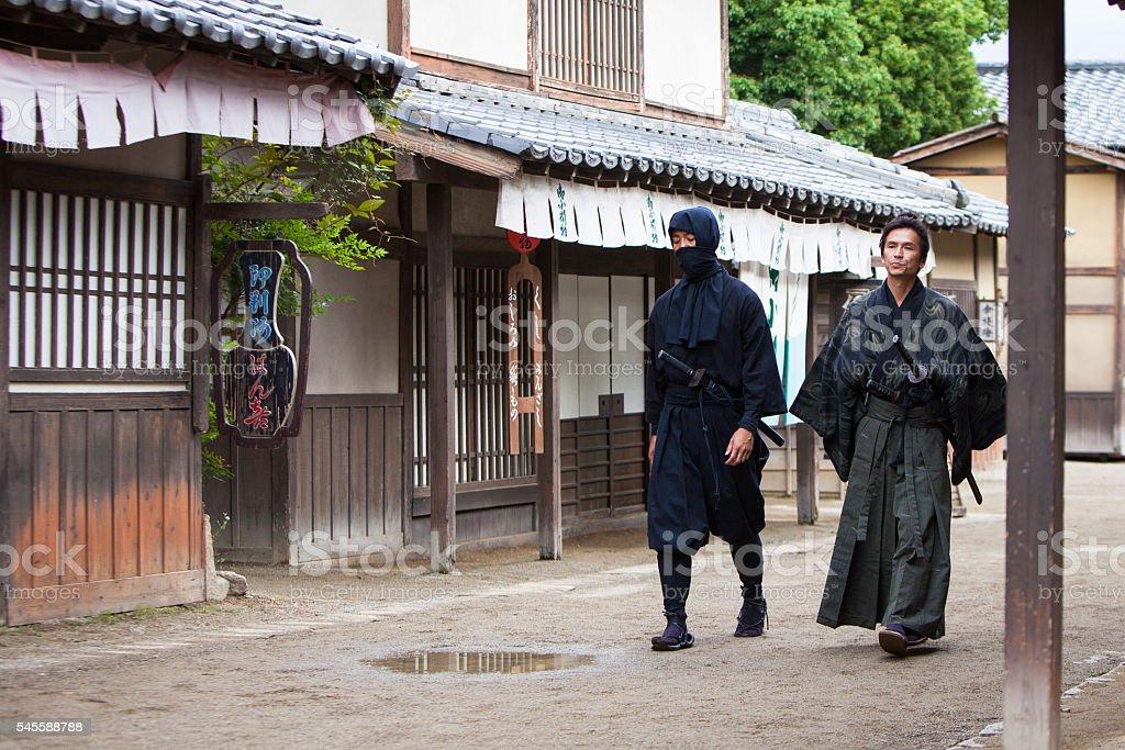 Ninja and Samurai masters walking down street stock photo