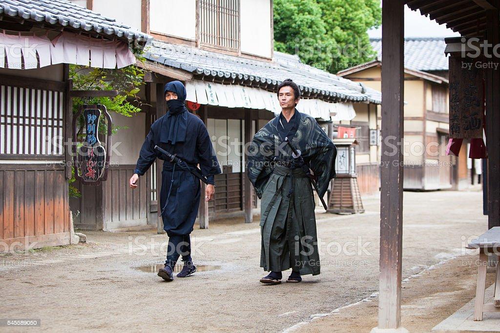 Ninja and Samurai masters walking down the village street stock photo