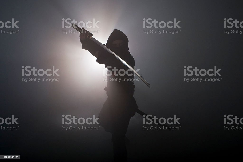 Ninja holding sword in dark fog stock photo
