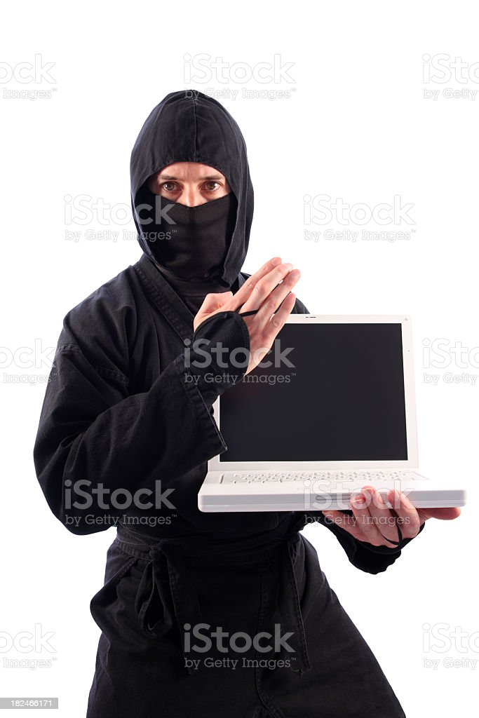 Ninja in Black Guarding Laptop Computer with Knife-Hand Technique stock photo