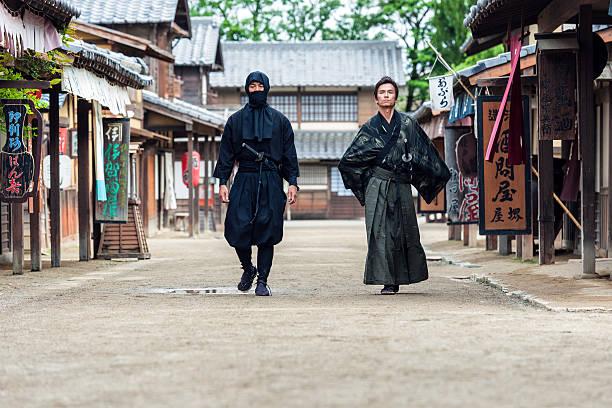ninja, de samurai paseo en medio de un pueblo calle - ninja fotografías e imágenes de stock