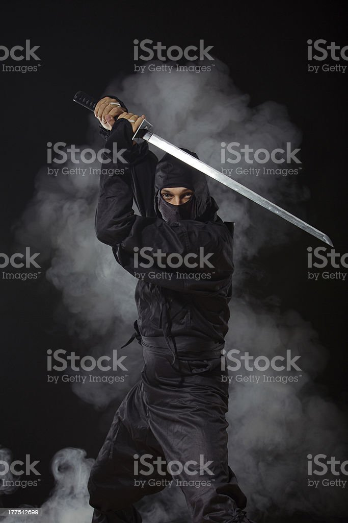Ninja with sword at night in smoke stock photo