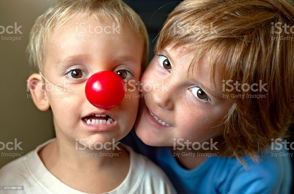 Ninos felices. Jugando con nariz de payaso stock photo