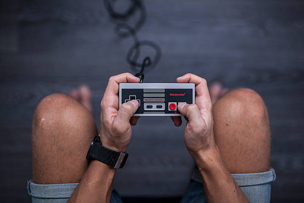 Nintendo Entertainment System - Video Game Controller Gothenburg, Sweden - January 31, 2015: A shot from above of a young man's hands using a Nintendo game controller, a remote controller for the Nintendo Entertainment System developed by Nintendo Co., Ltd. in the 1980s. Natural lighting. Shot on a grey wooden background. nintendo stock pictures, royalty-free photos & images