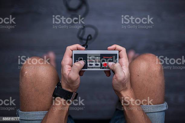 Gothenburg, Sweden - January 31, 2015: A shot from above of a young man's hands using a Nintendo game controller, a remote controller for the Nintendo Entertainment System developed by Nintendo Co., Ltd. in the 1980s. Natural lighting. Shot on a grey wooden background.