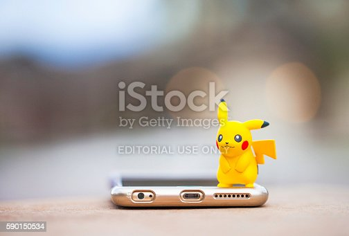 Peyton, Colorado, USA - August 17, 2016: A horizontal shot of the Pokemon Go character Pikachu, standing on top of an Apple iPhone 6 Plus. The character and phone are on a wall outdoors, in front of a defocused street scene in Peyton, Colorado. The figurine is made by Tomy.