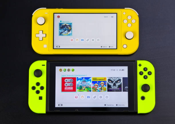 Nintendo Switch and small Nintendo Switch Lite. Comparison of two handheld game consoles MOSCOW, RUSSIA - October 10, 2019: Nintendo Switch and small Nintendo Switch Lite. Comparison of two handheld game consoles switch stock pictures, royalty-free photos & images
