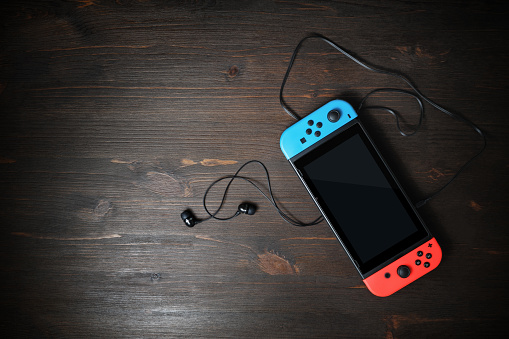Minsk, Belarus - May 07, 2020: Nintendo Switch game console with black screen and bright joy-con controllers on wood table background. Copy space for text. Top view. Flat lay.