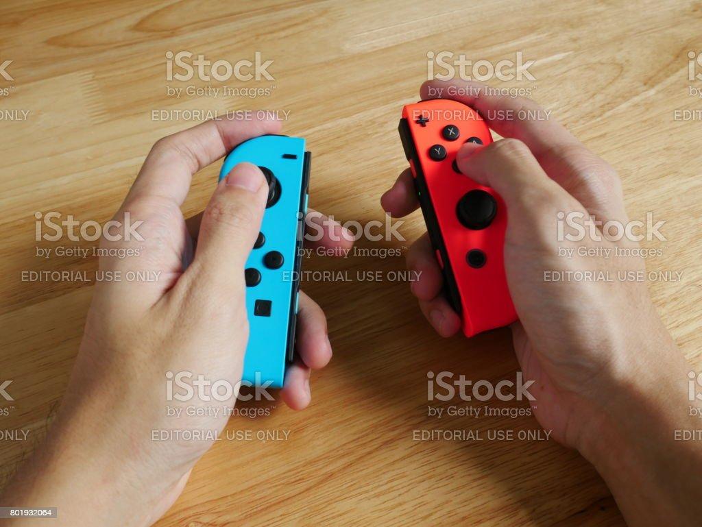 Bangkok, Thailand - June 25, 2017 : Nintendo Switch controllers held in hands. stock photo