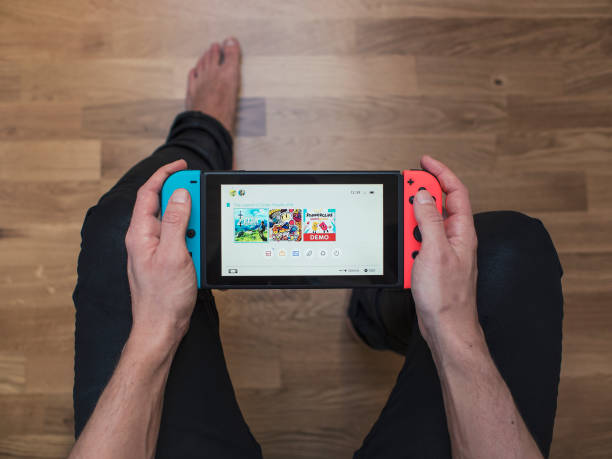 Nintendo Switch neon Game Console Gothenburg, Sweden - March 10, 2017: A shot from above of a young man's hands holding a neon coloured Nintendo Switch video game system developed and released by Nintendo Co., Ltd. in 2017. The system is turned on and its main menu is showing on the display. Shot on a hardwood floor background in a home environment. nintendo stock pictures, royalty-free photos & images