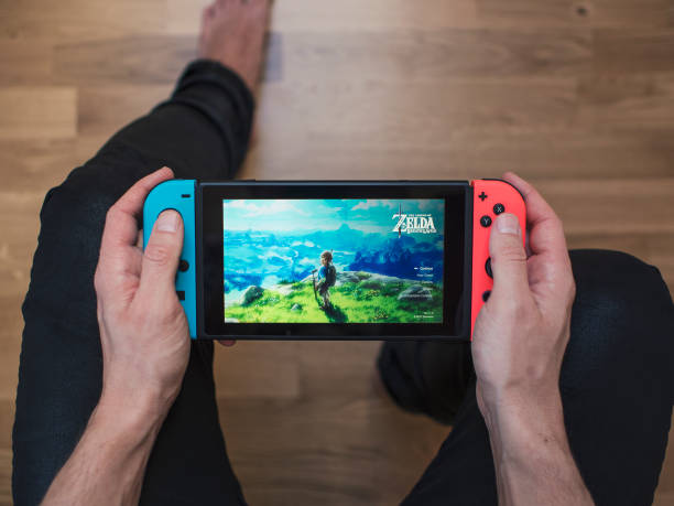 Nintendo Switch neon Game Console Gothenburg, Sweden - March 10, 2017: A shot from above of a young man's hands holding a neon coloured Nintendo Switch video game system developed and released by Nintendo Co., Ltd. in 2017. The system is turned on and the game The Legend of Zelda, Breath of the Wild is showing on the display. Shot on a hardwood floor background in a home environment. nintendo stock pictures, royalty-free photos & images