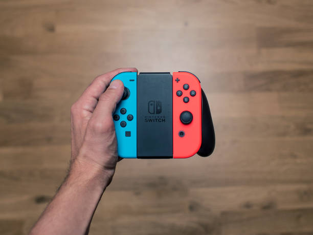 Nintendo Switch neon Game Controller Gothenburg, Sweden - March 6, 2017: A shot from above of a young man's hand holding a Nintendo Switch game controller, a neon coloured remote controller for the Nintendo Switch video game system developed and released by Nintendo Co., Ltd. in 2017. Shot on a wooden background in a home environment. nintendo stock pictures, royalty-free photos & images