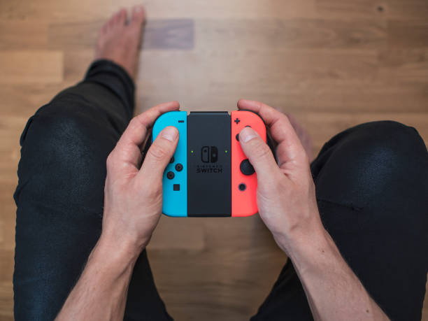 Nintendo Switch neon Game Controller Gothenburg, Sweden - March 10, 2017: A shot from above of a young man's hands holding a Nintendo Switch game controller, a neon coloured remote controller for the Nintendo Switch video game system developed and released by Nintendo Co., Ltd. in 2017. Shot on a hardwood floor background in a home environment. switch stock pictures, royalty-free photos & images