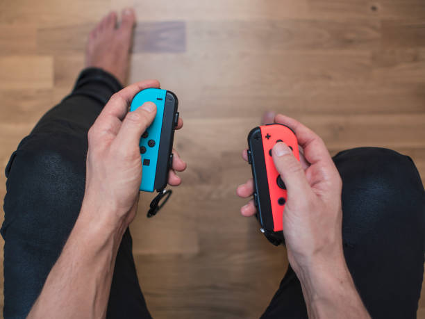 Nintendo Switch neon Game Controller Gothenburg, Sweden - March 10, 2017: A shot from above of a young man's hands holding two Nintendo Switch game controllers, neon coloured remote controllers for the Nintendo Switch video game system developed and released by Nintendo Co., Ltd. in 2017. Shot on a hardwood floor background in a home environment. nintendo stock pictures, royalty-free photos & images