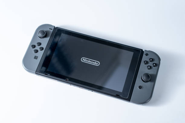 Nintendo Switch, the video game console for home or portable gaming dispalying a Nintendo Logo on the screen on a white background. Hong Kong, Hongkong - May 20, 2018: Nintendo Switch, the video game console for home or portable gaming dispalying a Nintendo Logo on the screen on a white background. nintendo stock pictures, royalty-free photos & images