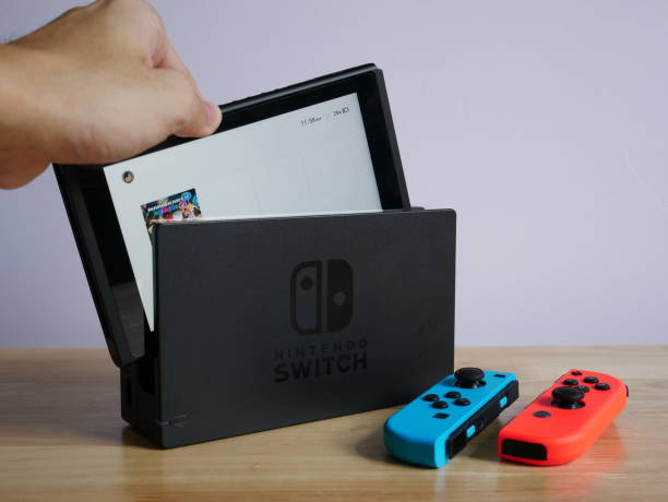 Bangkok, Thailand - June 25, 2017 : Nintendo Switch, the video game console on wooden table. Bangkok, Thailand - June 25, 2017 : Nintendo Switch, the video game console on wooden table. nintendo stock pictures, royalty-free photos & images