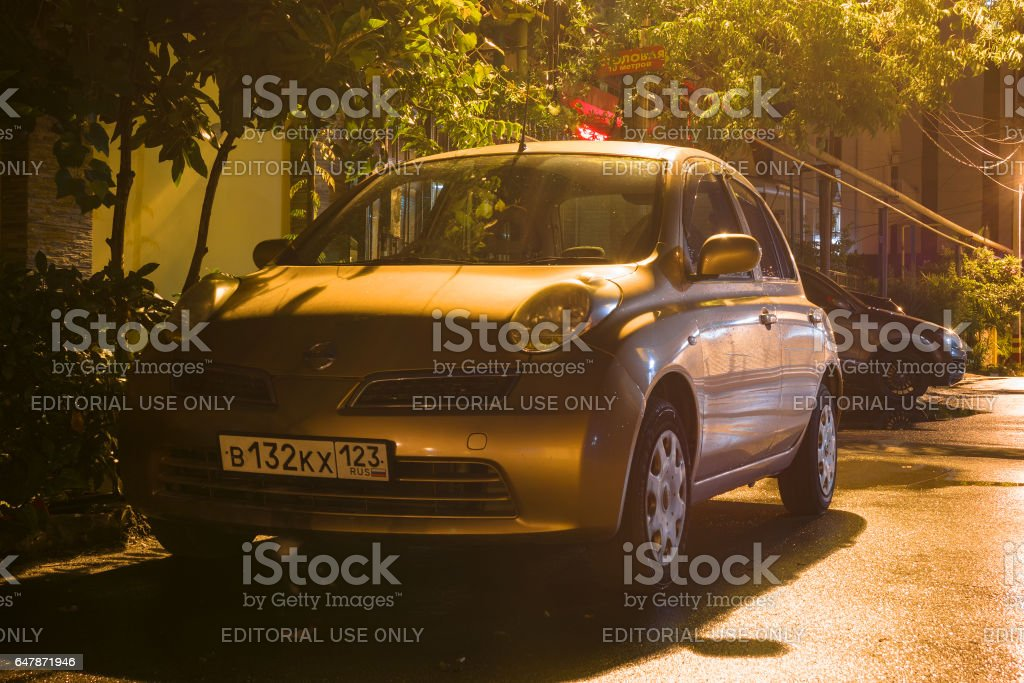 Nissan Micra parked on the street at night. stock photo