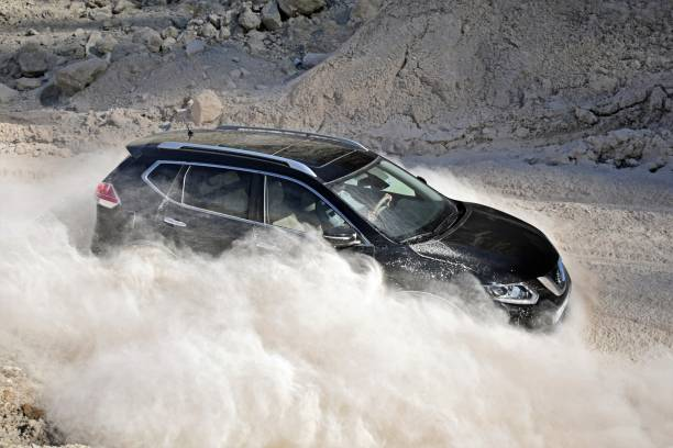 Nissan SUV driving in the dust cloud stock photo