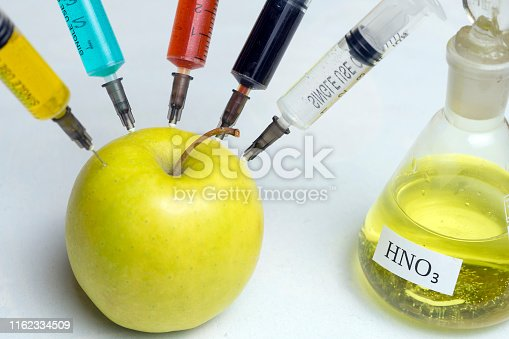 nitrates, pesticides, fungicides and other chemicals are injected into a green apple with a syringe. The concept of GMO and genetically modified organism.