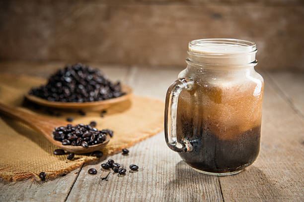 Nitro coffee fresh pour tap rustic lifestyle espresso mocha beans Fresh from the tap nitrous infused dark rich nitro black coffee in a glass jar java creamy beautiful froth foam head lifestyle decor with roasted beans on a rustic reclaimed wood wooden table background nitrogen stock pictures, royalty-free photos & images