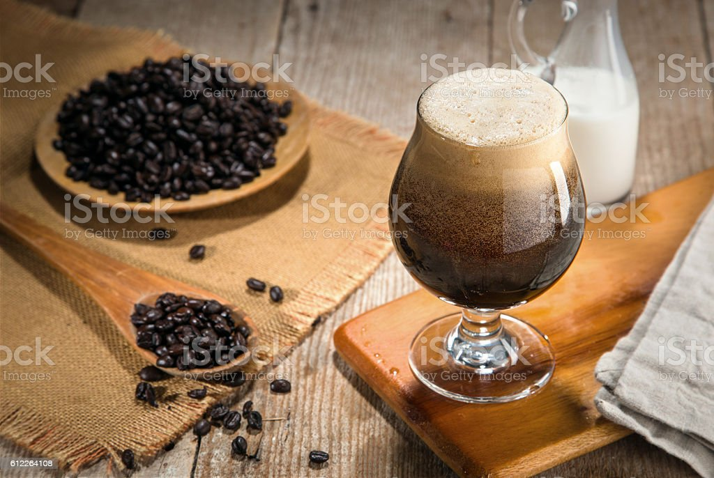 Nitro coffee nitrous infused delicious serving in tulip glass wooden stock photo