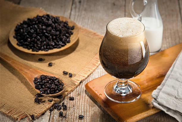 Nitro coffee nitrous infused delicious serving in tulip glass wooden Fresh from the tap nitrous infused dark rich nitro black coffee in a glass jar java creamy beautiful froth foam head lifestyle decor with roasted beans on a rustic reclaimed wood wooden table background nitrogen stock pictures, royalty-free photos & images