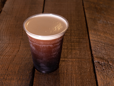 Nitro Cold Brew Coffee beverage on a rustic wood background.