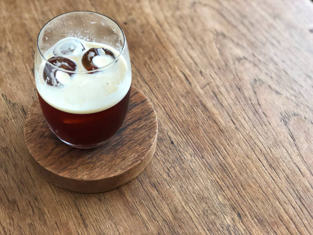 nitro cold brew coffee glass on the wooden table with natural light and copy space. - azoto foto e immagini stock