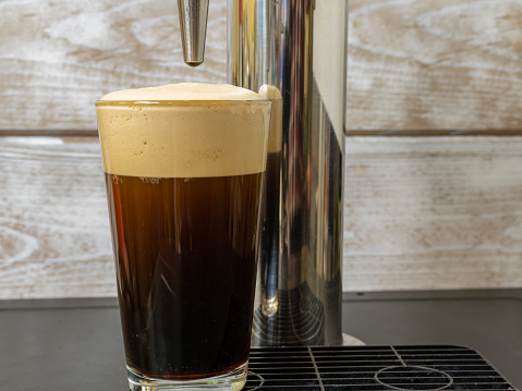 Nitro cold Brew Coffee in a clear glass on a dispenser