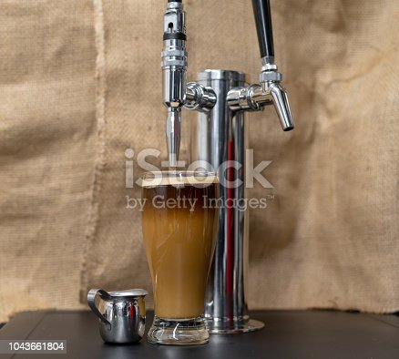 Nitrogen infused cold brew coffee in a clear glass next to a tap with sweet cream added and a foamy top.