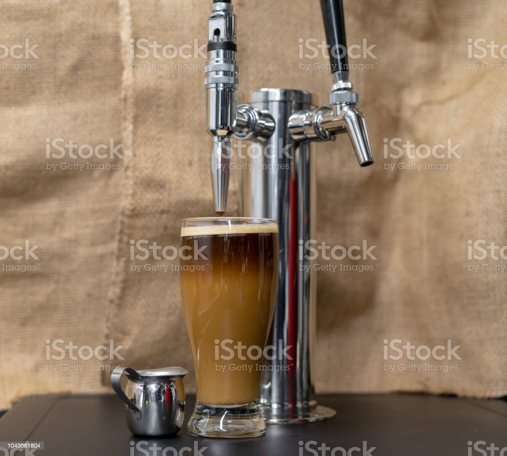 Nitro Cold brew coffee next to a beer style dispensing Tap. stock photo