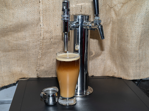 Nitro Cold brew coffee next to a beer style dispensing Tap.
