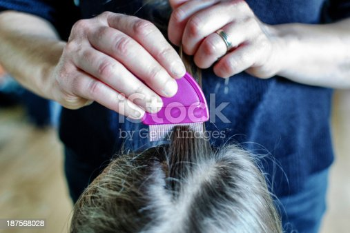 A mother combing a child's head and checking for head lice (focus on comb)