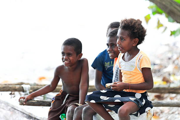 Ni-Vanuatu kids on the beach. Lamen Bay-Epi island-Vanuatu. 5400 Lamen Bay, Epi island, Vanuatu-October 4, 2014: Four kids of the Ni-Vanuatu people take a rest to chat with the tourists after coming back from school while sitting on a fence waiting for lunch time. vanuatu stock pictures, royalty-free photos & images