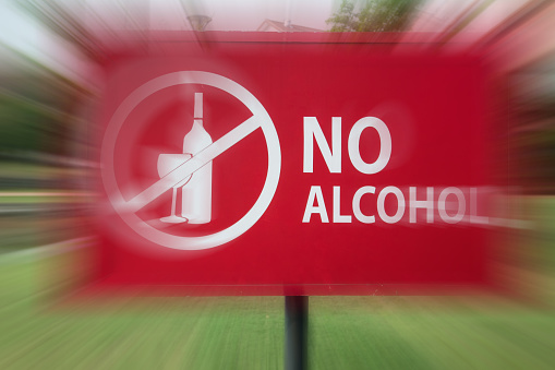 No alcohol sign in motion blur in the park near residential area.