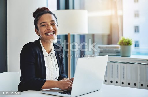 Shot of a young businesswoman using a laptop in a modern office