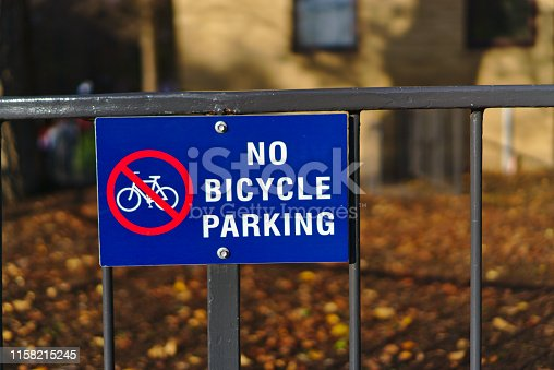 No bicycle parking sign in blue and red color embedded on iron fence