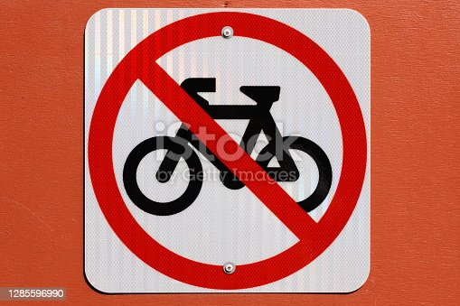Sign on an orange wall for no bike riding.
