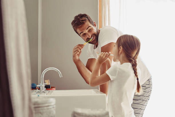No cavities for this family Shot of a happy father and his little girl washing their hands together in the bathroom toothbrush stock pictures, royalty-free photos & images