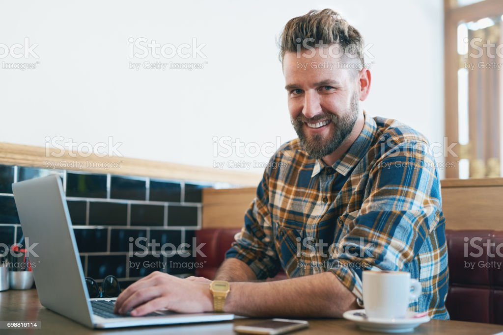Portrait of a young man using his laptop while sitting in a cafe