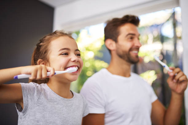 No Dad, brush like this Cropped shot of a handsome Dad and his daughter brushing their teeth in the bathroom dental health stock pictures, royalty-free photos & images