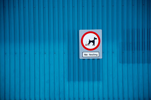 No dog fouling sign on blue warehouse stock photo