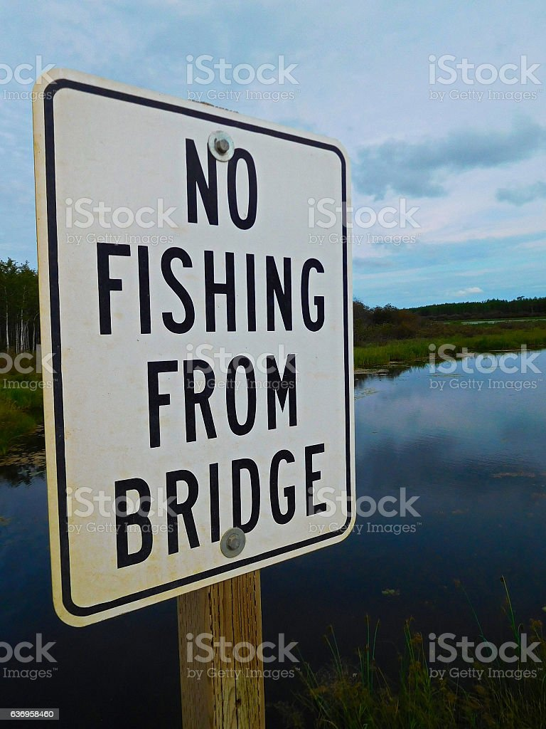 No Fishing From Bridge Sign Infront of a Beautiful River stock photo
