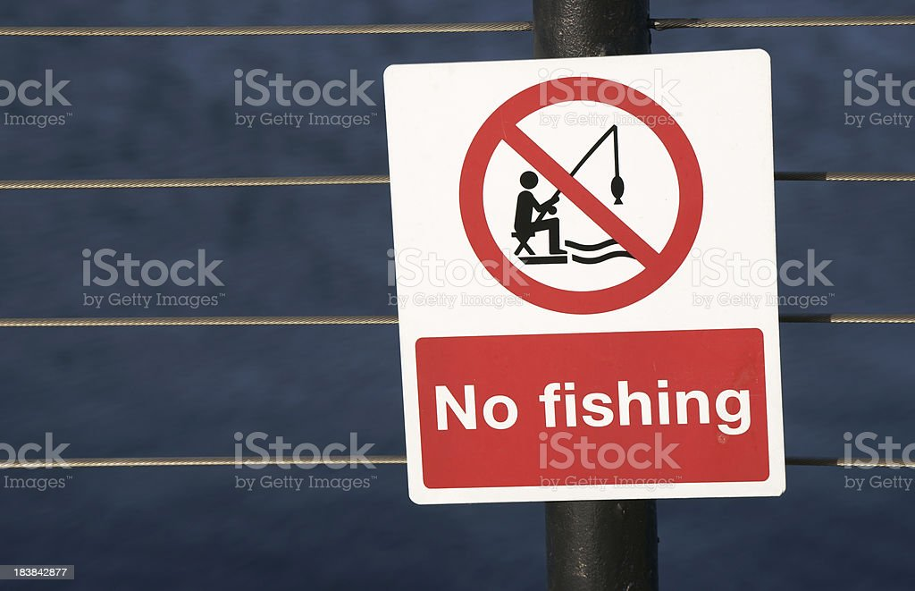 No fishing sign on fence against dark water stock photo