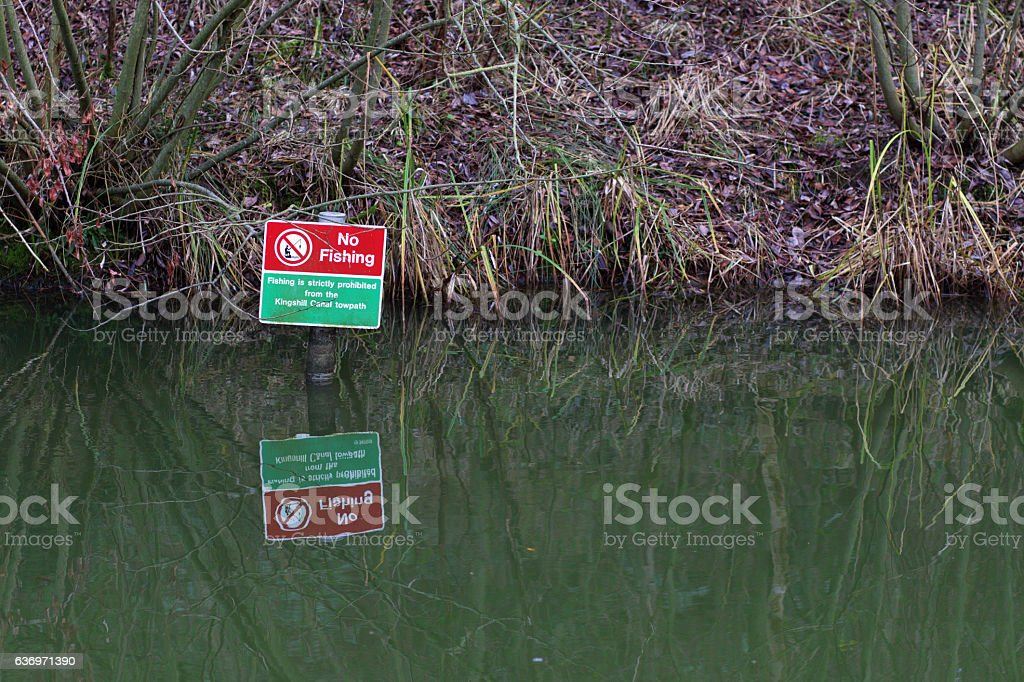 No fishing warning sign reflected Kingshill Canal Swindon Wiltshire stock photo