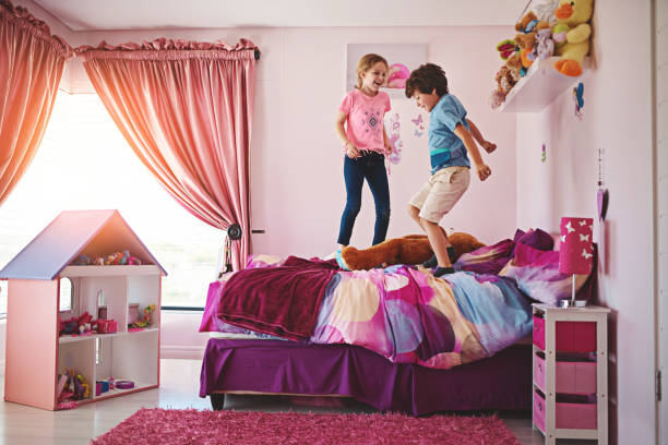 No greater joy than jumping on a bed Shot of an energetic brother and sister jumping up and down on the bed girl bedroom stock pictures, royalty-free photos & images